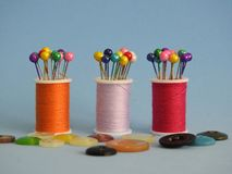 Sewing thread spools, buttons and sewing pins: many colors, a joyful combination. royalty free stock photo