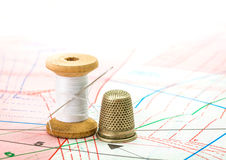 Sewing thread and thimble on pattern cutting Stock Image