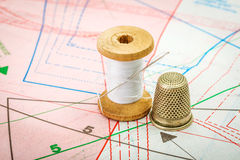 Sewing thread and thimble on pattern cutting Stock Photography