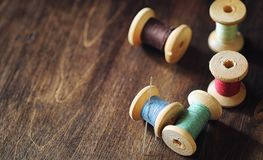 Sewing thread on a wooden background. Set of threads on bobbins royalty free stock image
