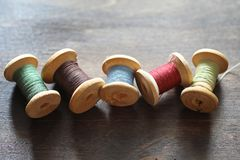 Sewing thread on a wooden background. Set of threads on bobbins. Retro style. Vintage accessories for sewing on the tabler stock photography