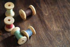 Sewing thread on a wooden background. Set of threads on bobbins. Retro style. Vintage accessories for sewing on the tabler royalty free stock images