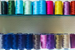 Sewing threads in assortment close-up on the shelf. Stock Images