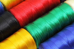 Sewing threads background. Detail of colorful silk sewing embroidery threads Stock Images