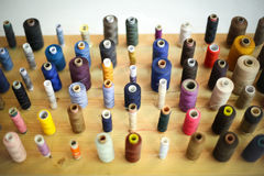 Sewing threads displayed on wooden board Royalty Free Stock Images