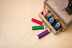 Sewing threads multicolored in wooden box background closeup with space for text stock images