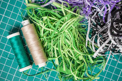 Sewing threads and textile offcuts on cutting checkered green m Royalty Free Stock Photo