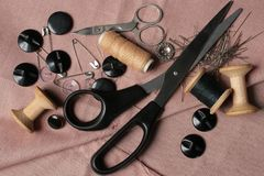 Sewing tools. Thread on spool, scissors, buttons and needles on threaded texture Stock Photo