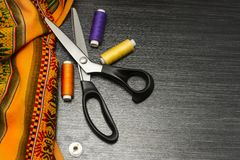 Sewing tools: colorful cloth. scissors and sewing kit includes threads of different colors, thimble and other sewing accessories o. N wooden table. Top view royalty free stock image