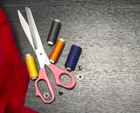 Sewing tools: colorful cloth. scissors and sewing kit includes threads of different colors, thimble and other sewing accessories o. N wooden table. Top view royalty free stock photos