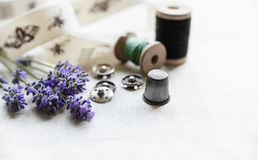 Sewing tools with fresh lavander flowers on linen background. Vintage wooden spool, braid, thimble, buttons. Stock Photography