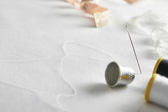 Sewing tools with lace on white fabric elevated diagonal view royalty free stock photo