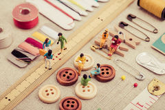 Sewing tools and miniature women Royalty Free Stock Photos