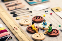 Sewing tools and miniature women Stock Images