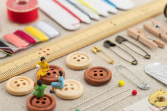 Sewing tools and miniature women Royalty Free Stock Photography