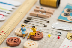 Sewing tools and miniature women Stock Image