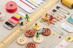 Sewing tools and miniature women Stock Photos