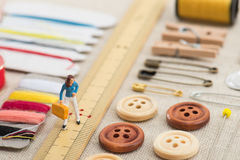 Sewing tools and miniature women Royalty Free Stock Image