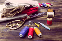 Sewing tools, multi-coloured fabric and threads on a wooden back. A collection of sewing tools and different textile fabric and multi-coloured threads on a Stock Photos