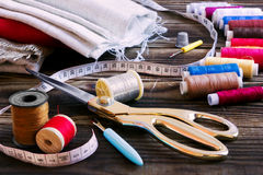 Sewing tools, multi-coloured fabric and threads on a wooden back. A collection of sewing tools and different textile fabric and multi-coloured threads on a Stock Photo