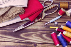 Sewing tools, multi-coloured fabric and threads on a wooden background. A collection of sewing tools and different textile fabric and multi-coloured threads on a Royalty Free Stock Images