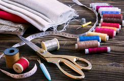 Sewing tools, multi-coloured fabric and threads on a wooden background. A collection of sewing tools and different textile fabric and multi-coloured threads on a Stock Photos