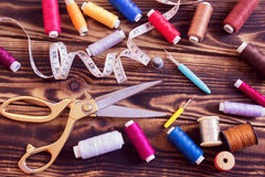 Sewing tools and multi-coloured threads on a wooden background. A collection of sewing tools and multi-coloured threads on a wooden background Royalty Free Stock Images
