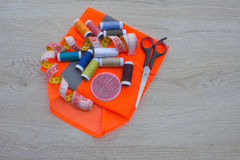 Sewing tools and sewing kit on wooden textured background. Thread, needles and cloth Stock Photography
