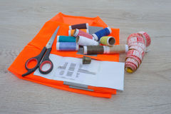 Sewing tools and sewing kit on wooden textured background. Thread, needles and cloth Stock Photo