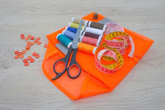 Sewing tools and sewing kit on wooden textured background. Thread, needles and cloth Royalty Free Stock Photography