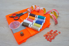 Sewing tools and sewing kit on wooden textured background. Thread, needles and cloth Stock Images