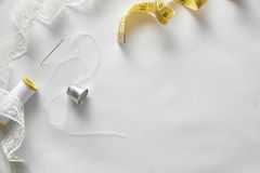 Sewing tools with tape on white fabric background top view Stock Photos