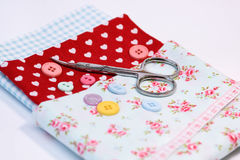Sewing tools with vintage fabric background with scissors and buttons Royalty Free Stock Images