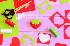 Sewing toy, tools and materials. Felt strawberry toy, scissors, red and green felt sheets and scraps, thread, needle, paper patter. Needlework supplies. Sewing Royalty Free Stock Photos