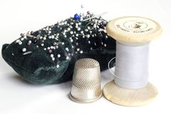 Sewing utensils. Pin cushion, pins, needles, thimble, spool of cotton thread stock image