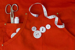 Sewing utensils on red. Apron, hobby Stock Images
