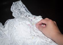 Sewing wedding dress, hand seamstress holding a needle over the fabric pattern Stock Photo