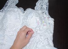 Sewing wedding dress, hand seamstress holding a needle over the fabric pattern Stock Image