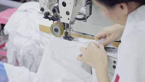 Sewing of white shirt. Seamstress sews two parts of white men`s shirt on sewing machine with a special presser foot stock video footage