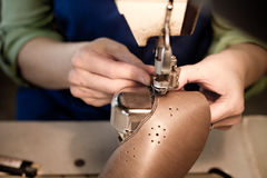 Sewing worker front view. Female worker sewing leather in a footwear factory Stock Photography