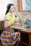 Sewing in workshop beautiful brunette young woman pinup girl with red lips and nails in yellow dress blue ribbon on her head. Having tea break pinup girl with Royalty Free Stock Images