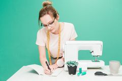 Sewing workshop. Seamstress at work. Portrait of a young dressmaker with notebook on a colored background. royalty free stock photo
