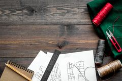 In sewing workshop. Textile, thread, sciccors, pattern on dark wooden background top view copyspace. In sewing workshop. Textile, thread, sciccors, pattern on Royalty Free Stock Image
