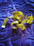 Sewing. yellow measuring tape for sewing on purple material. Sewing yellow numbers measure purple measuring tape material stock images