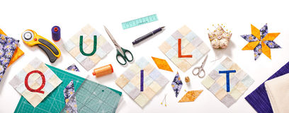 Sewn letters, consisting to the word quilt surrounded by accessories for patchwork stock images
