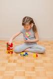 Sex år gammal liten flicka som spelar med byggnadskvarter hemma Arkivbilder