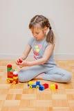 Sex år gammal liten flicka som spelar med leksaker för byggnadskvarter arbetare för aktivitetskonstruktionssilhouette Royaltyfri Foto