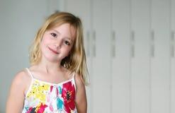 Sex åriga blonda flicka i en vit klänning för sommar med blommor som ler på en abstrakt bakgrund Royaltyfri Bild