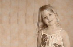 Sex åriga blonda flicka i en vit klänning för sommar med blommor som ler på en abstrakt bakgrund Arkivfoto