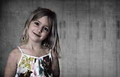 Sex åriga blonda flicka i en vit klänning för sommar med blommor som ler på en abstrakt bakgrund Royaltyfria Bilder